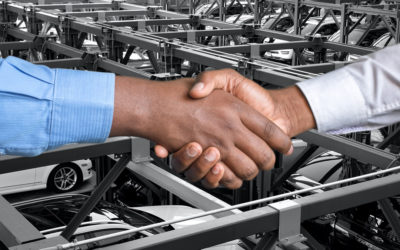 Two men shaking hands in car factory